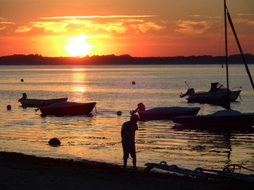 Wasserspiegelung vom Sonnenuntergang in der Eckernförder Bucht (bei Noer), im Vordergrund ein Mensch und mehrer geankerte kleine Boote