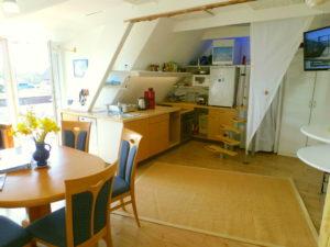 Wohnküche (OG), links: runder Tisch, mit mehreren Stühlen; mittig: Küchezeile, Treppe nach oben; Rechts: TV