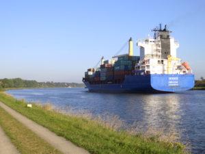 Rechts: Der Nord-Ostsee-Kanal, mit einen Frachtschiff (von hinten); Links: Beton-Feldweg parallel zum Kanal. Im Hintergrund ganz klein Sehestedt.
