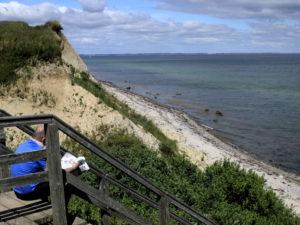 Steilküste in Stohl (bei Dänischenhagen, zwischen Kiel und Eckernförde), im Vordergrund Holztreppe mit Mensch