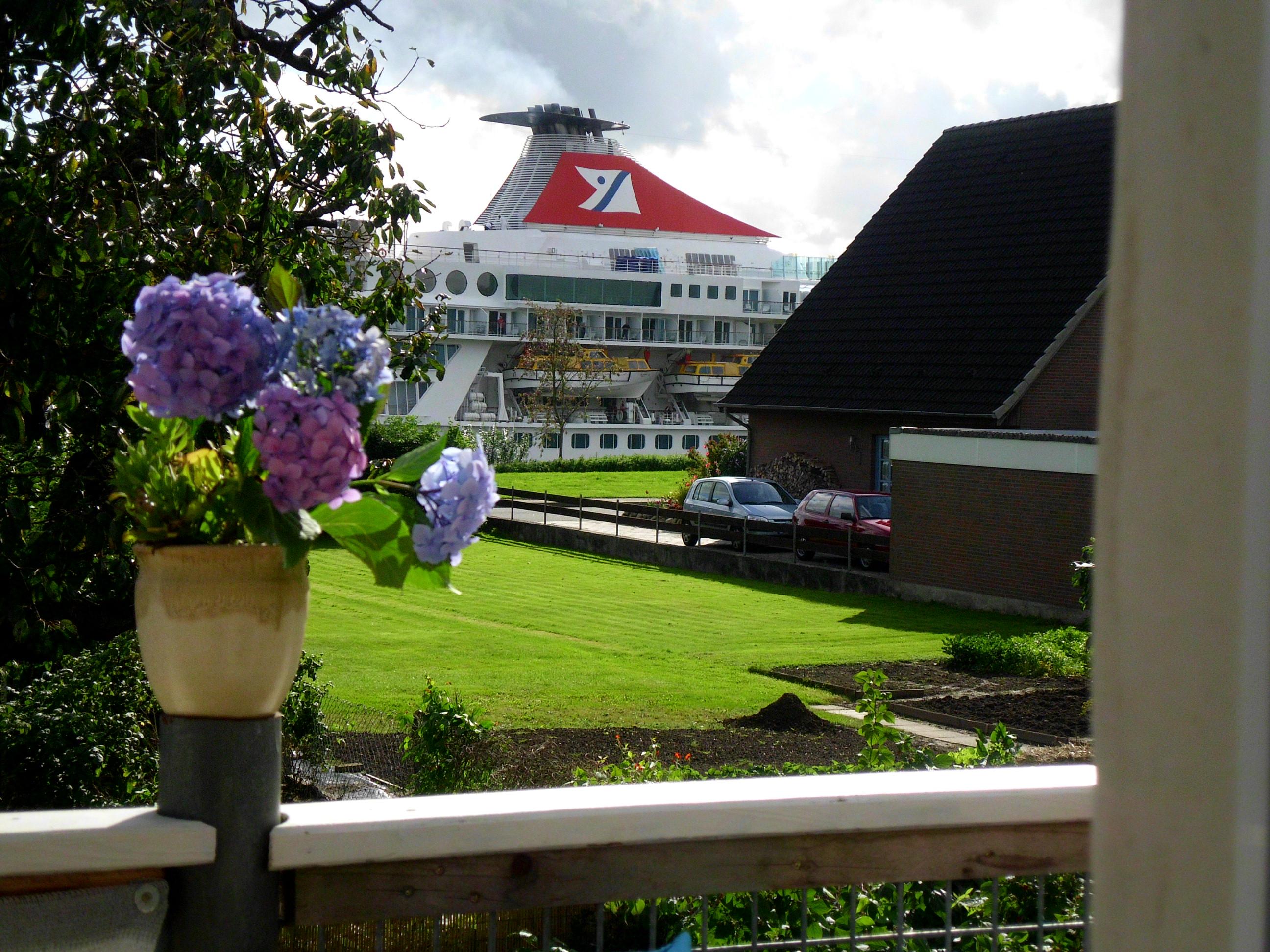 Das Schiff Balmoral fährt durchs Land, vom Land aus gesehen.  Beim Ort Sehestedt. Es sind nur die Oberbautem die sehen. Im Vordergrund der Balkon eines Wohnhauses.